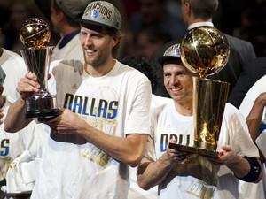 Dirk Nowitzki (l.) hält die Trophäe als wertvollster Spieler während sein Mannschaftskollege Jason Kidd die Meisterschaftstrophäe hält. Foto: picture-alliance