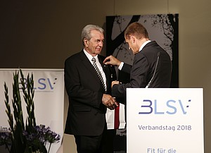 Alfons Hörmann steckt Günter Lommer die Goldene Ehrennadel an das Revers