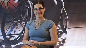 Katharina Krüger sitzt im Rollstuhl vor dem Plakat eines Basketballspielers im Rollstuhl
