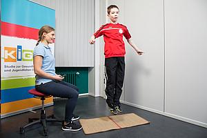 Seitliches Hin- und Herspringen: Ziel ist es, die grobmotorischen Fähigkeiten und die (Ganzkörper-)Koordination unter Zeitdruck zu messen. Foto: Edgar Zippel/RKI