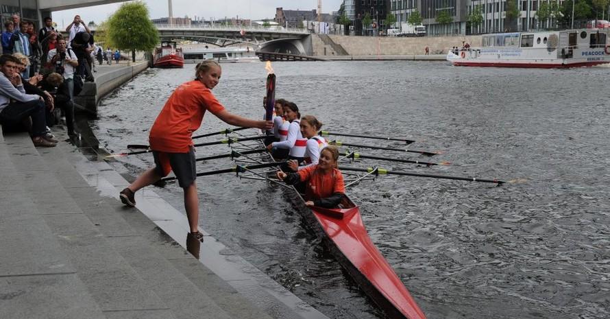 Veronika übernimmt die Fackel von den Ruderinnen des deutschen Frauen-Vierers.