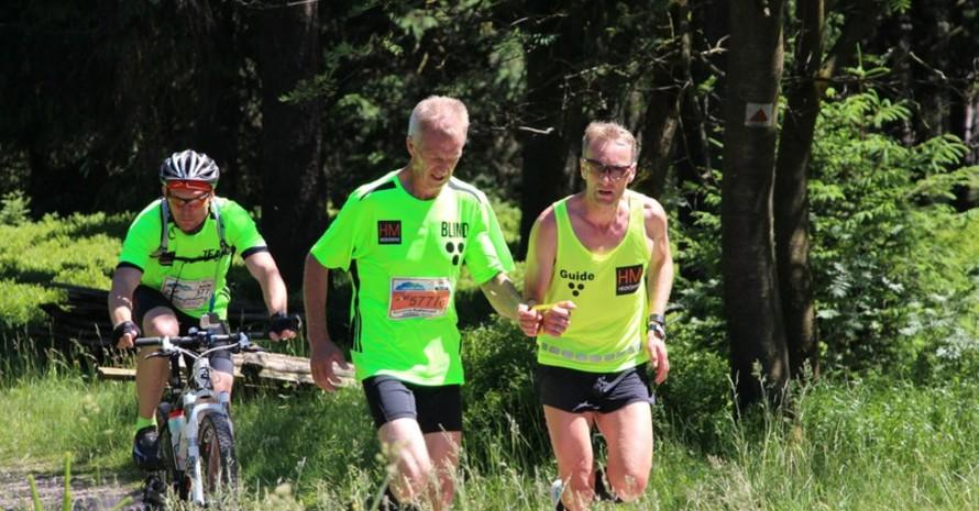 Lauftandem mit Radbegleitung, der Läufer trägt ein hellgrüne T-Shirt, der Guide ein neon-gelbes.