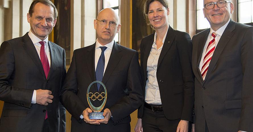 Laudator Michael Vesper (re.), IOC-Mitglied Claudia Bokel und DOSB-Präsident Alfons Hörmann (li.) überreichen dem Künstler Hans Borchert die IOC-Trophy. Foto: DOSB/Torsten Silz