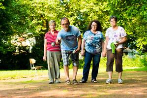Drei Frauen und ein Mann spielen Boule im Park