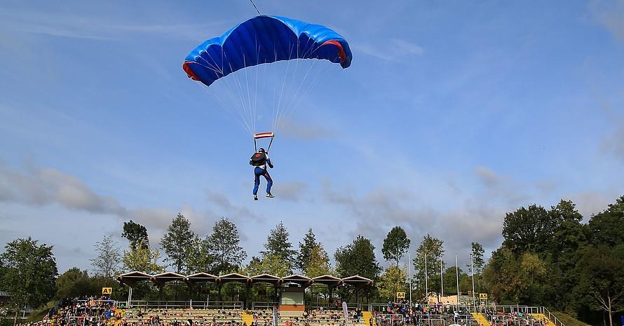 Ein Fallschirmspringer landete kurz nach der offiziellen Begrüßung im Stadion Müllerwiese. Foto: Treudis Naß