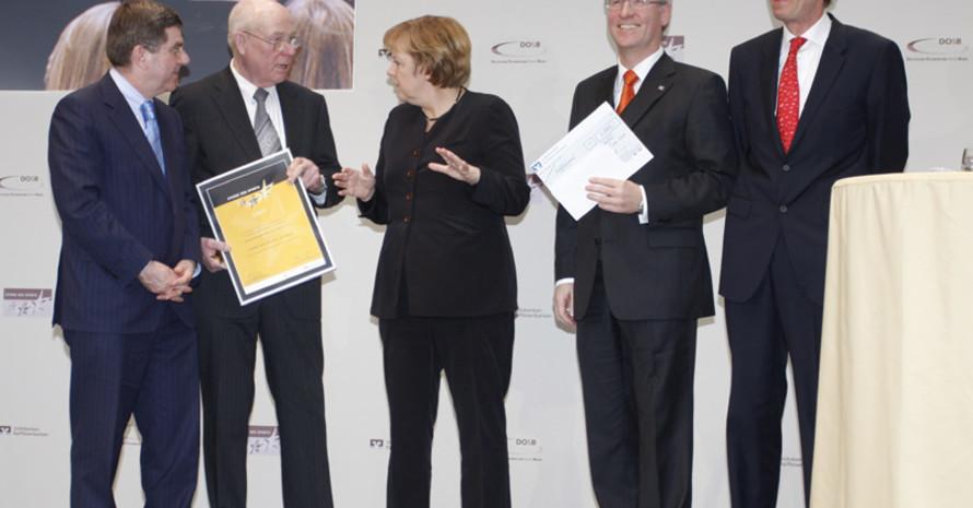 DOSB-Präsident Dr. Thomas Bach, Vereinssprecher Eike Holtzhauer, Bundeskanzlerin Angela Merkel, Werner Albers von der Volksbank Nordheide und Präsident der Bundesverbandes VR Dr. Christoph Pleister (v.l) bei der Siegerehrung.