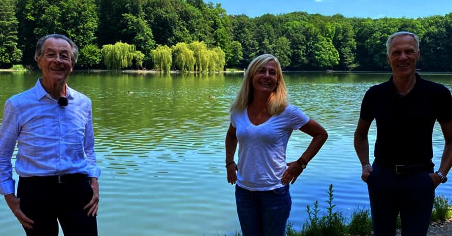 Drei Menschen, im Hintergrund ein See. Ringsherum Wald.