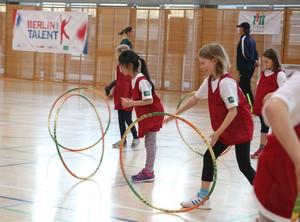 Kinder haben Spaß beim Spiel mit Hula-Hoop-Reifen. Foto: Jürgen Engler / LSB Berlin