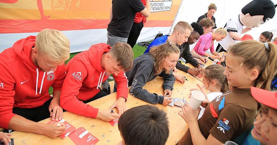 Die prominenten Sportlerinnen und Sportler hatten alle Hände voll zu tun, um die Autogrammwünsche zu erfüllen. Foto: Treudis Naß