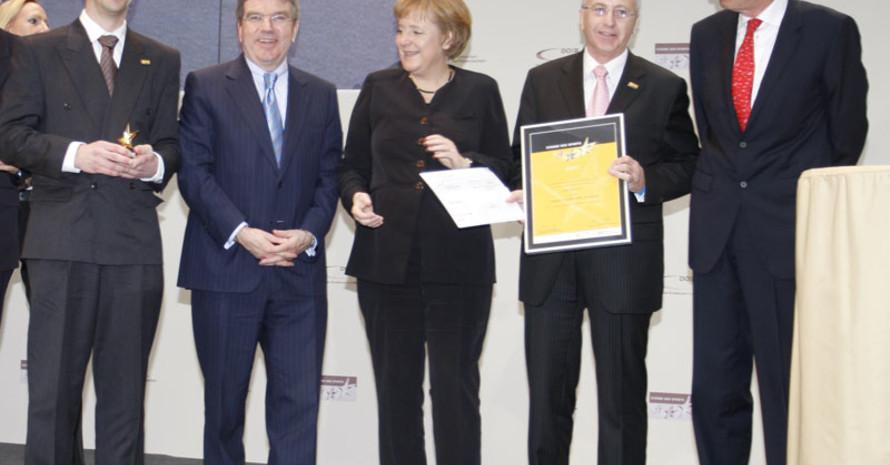 Vereinsvorsitzender Matthias Müller, DOSB-Präsident Dr. Thomas Bach, Bundeskanzlerin Angela Merkel, Emil Baderschneider und Präsident der Bundesverbandes VR Dr. Christoph Pleister (v.l) bei der Siegerehrung.