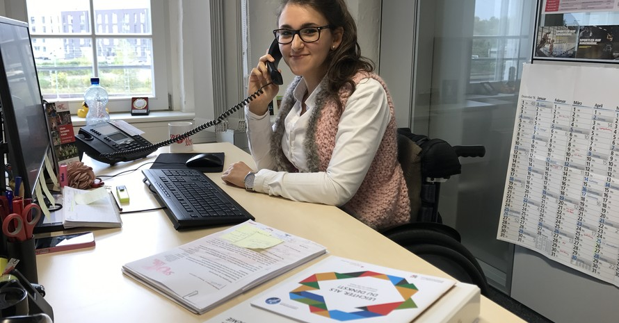 Sina Eghbalpour sitzt im Rollstuhl am Schreibtisch mit dem Telefonhörer in der Hand