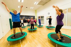 Männer und Frauen stehen auf einem Mini-Trampolin in einem Gymnastiksaal. Sie machen Bewegungen mit den Armen