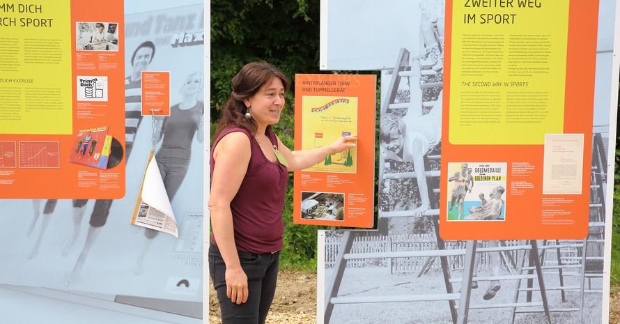 Ulrike von Bothmer, Kuratorin des Hessenparks, erläutert den Gästen die Schautafeln zur Trimm-Bewegung und verät, welche Schätze ihr Team bei der Recherche gefunden hat. Fotos: DOSB / Markus Böcker