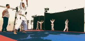 Zwei Kinder in der weißen Karatekleidung machen Übungen vor schwarzem Hintergrund. Im Vordergrund ein Kameraman und ein Trainer.