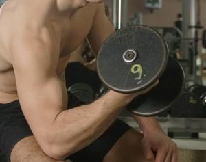 Ein Sportler trainiert seinen Bizeps mit einer Kurzhantel. Foto: picture-alliance