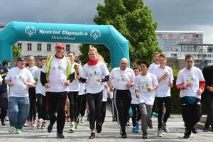 Die Läufer gehen nach dem Startschuss auf die Strecke. Vorne weg läuft als Fackelträgerin Schwimm-Olympiasiegerin und SportpatinBritta Steffen. Foto: SOD/Juri Reetz
