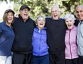 Sechs ältere Menschen stehen eng nebeneinander und lachen.