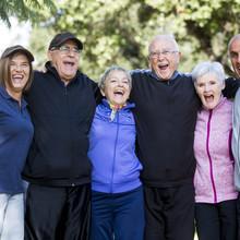 Sechs ältere Menschen stehen umarmt nebeneinander und lachen.
