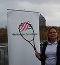 Ewa Astapczyk hält in der linken Hand einen Tennisball und in der rechten Hand einen Tennisschläger. Im Hintergrund ist ein Roll-Up mit dem Logo des Hamburger Sportbunds zu sehen.