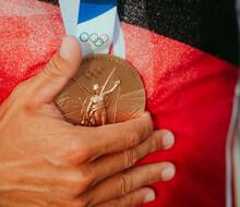Die rechte Hand von Slalom-Kanute Sideris Tasiadis hält ihre Bronzemedaille fest. Die Medaille ist im Mittelpunkt. Den Hintergrund bildet der Team Deutschland Trainingsanzug.