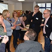 Menschen stehen im Kreis, eine Person sitzt. Sie diskutieren. Im Hintergrund ist eine Leinwand mit einer Präsentation zu sehen, eine Pinnwand, an die Moderationskarten gepinnt sind, sowie weitere Personen, die im Raum stehen.