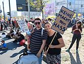 """Im Vordergrund des Bildes ist eine junge Familie zu sehen mit Kinderwagen. Der Vater hält ein kleines Kind auf dem Arm, die Mutter ein Protestschild mit der Aufschrift """"Keine Macht dem Hass""""."""