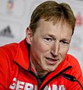 Bernd Wolfarth, leitender Mannschaftsarzt des DOSB bei Olympischen Spielen gibt ein Update zur Coronavirus Epidemie. Er trägt einen roten Pullover, beugt sich nach vorne und spricht in ein Mikrofon.