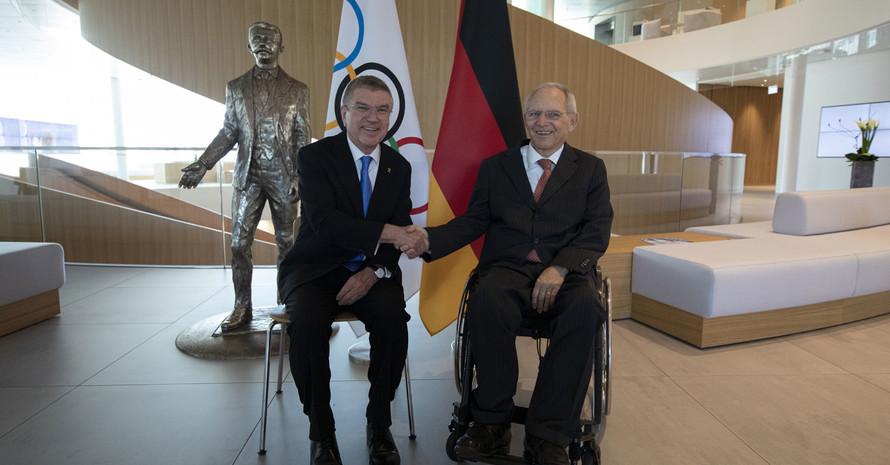 Thomas Bach sitzt auf einem Stuhl neben Wolfgang Schäuble im Rollstuhl und gratuliert ihm.Foto: IOC/Greg Martin