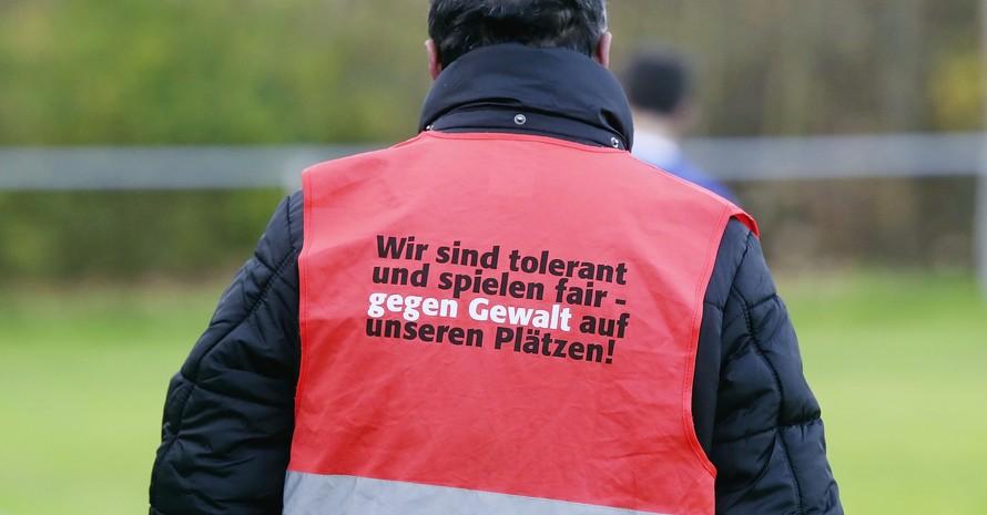 """Ein Ordner trägt eine Sicherheitsweste mit der Aufschrift """"Gegen Gewalt und für Toleranz"""". Foto: picture-alliance"""