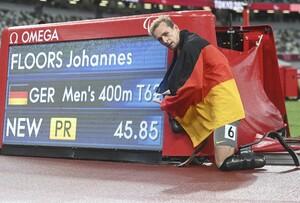 Goldmedaillengewinner Johannes Floors zeigt auf die Anzeigentafel, die seinen paralympischen Rekord auf der 400m-Strecke ausweist. Foto: picture-alliance