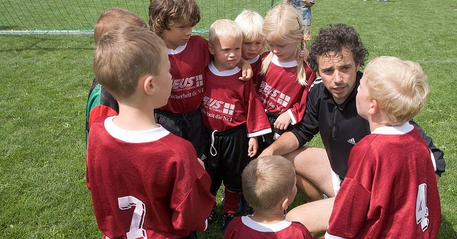 Ein Übungsleiter im Sportverein erklärt seinen kleinen Schützlingen die nächste Aufgabe. Foto: picture-alliance