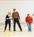 Fünf Personen stehen auf einer gelben Linie in einer Sporthalle nebeneinander. Eine junge Frau, die auch auf der gelben Linie zwischen den Personen steht, erklärt etwas mit einem Zettel in der Hand.