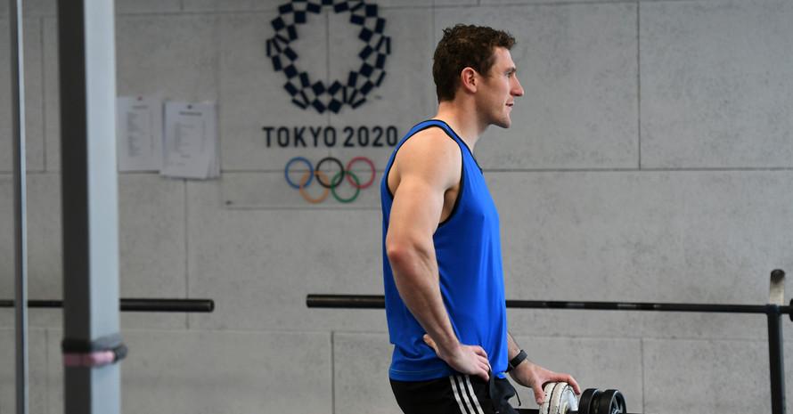 Sportler Sebastian Brendel mit blauem, ärmellosen T-Shirt steht an Kurzhanteln. Im Hintergrund ist das Tokio 2020 Logo auf der Wand.