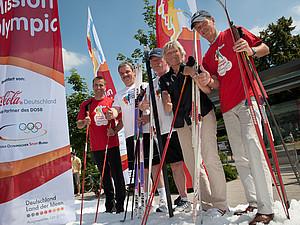Frank Szymanski, Oberbürgermeister von Cottbus (2. von links), erfrischt sich im Schnee vor der Stadthalle beim Mission Olympic Finale in Cottbus. Auch Sylvio Kroll, Olympischer Medaillengewinner im Kunstturnen (links), Wolfgang Neubert, Präsident des Stadtsportbunds Cottbus (Mitte), Margit Stopper, Mitglied des Präsidialausschusses Breitensport des DOSB, und Hendrik Steckhan, Geschäftsführer der Coca-Cola GmbH (rechts), freuen sich über die Abkühlung. Foto: Mission Olympic