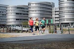 Zwei Läuferinnen und ein Läufer joggen draußen. Im Hintergrund sind große Gebäudekomplexe zu sehen.