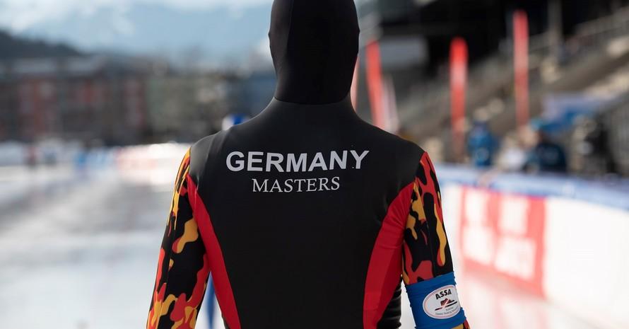 Ein*e Eisschnelläufer*in von hinten mit Kaputze. Auf dem Rücken des Trikots steht Germany Masters. Der Hintergrund ist verschwommen. Es sind ein Eislaufstadion und Berge zu erkennen.