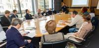 Frauen und Männer sitzen an einem Tisch und schauen auf die Referentin vorne
