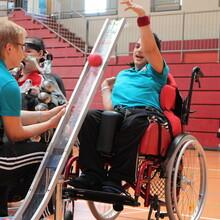 In einer Turnhalle hat eine Person im Rollstuhl einen roten Ball in eine silberne Rampe gelegt. Die Rampe wird von einer Person gehalten, welche die gleiche Sportkleidung trägt wie die Person im Rollstuhl.