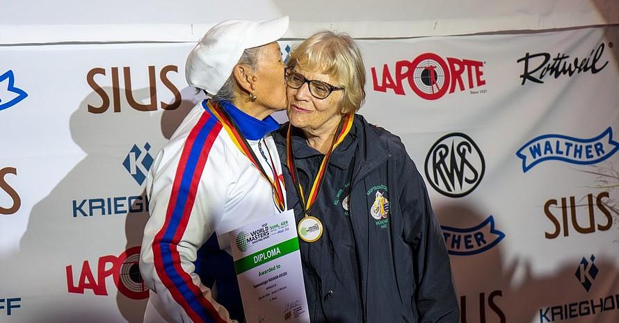 Ein älterer Herr gibt einer älteren Dame einen Kuss auf die Wange.