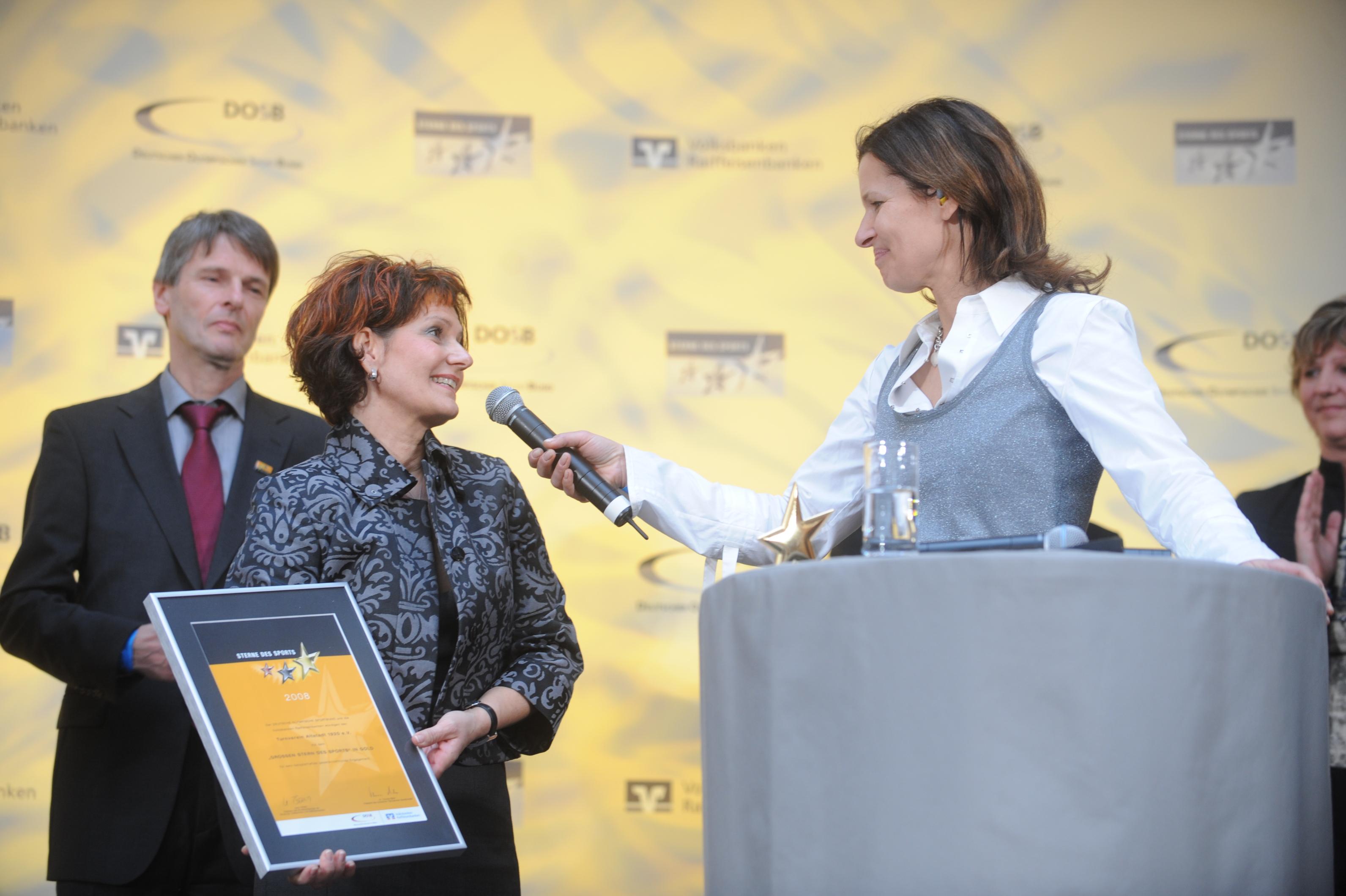 Die erste Vorsitzende des TV Altstadt Stephanie Deutscher (m.) mit DOSB-Präsident Thomas Bach (l.), Walter Merz von der Volksbank Saarpfalz und Moderatorin Katrin Müller-Hohenstein (r.).