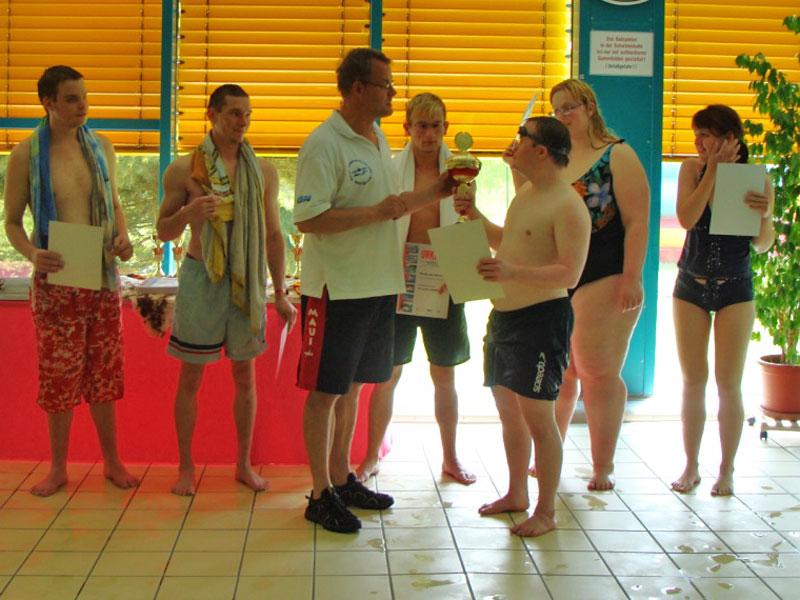 """Volker Hoffmann, der erste Vorsitzende des Harzer Schwimmvereins e.V.  Wernigerode (Mitte), ehrt die Teilnehmer der Schwimmstaffeln bei der """"Woche der Inklusion"""". (Foto: HSV)"""