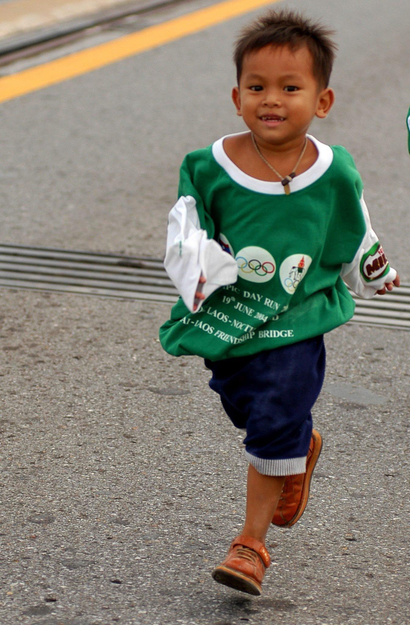 """Ein kleiner Läufer passiert 2004 beim """"Olympic Day Run"""" die Freundschaftsbrücke in Nongkhai. 4000 Läufer aus Thailand und 2000 aus Laos nahmen an der damals gemeinsam von NOKs beider Länder organisierten Veranstaltung teil."""